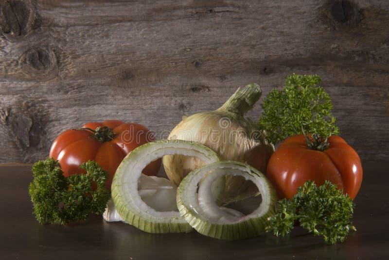 Tomate, Zwiebel und Petersilie auf Holzoberfläche stockbilder