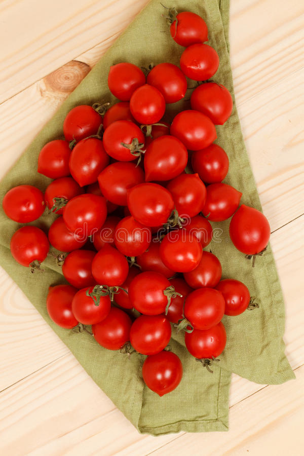 Tomaten auf hölzernem Hintergrund des grünen Gewebes stockbild