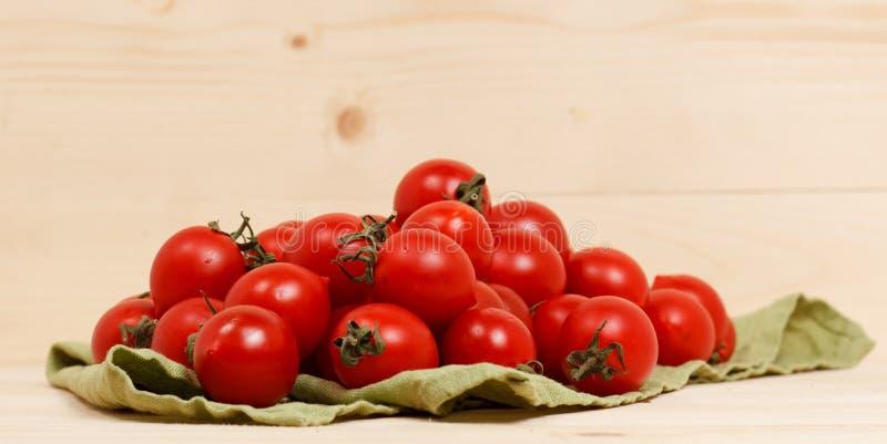 Tomaten auf hölzernem Hintergrund des grünen Gewebes stockfotos