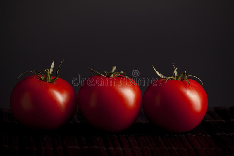 Tomaten auf schwarzem Hintergrund stockfotografie