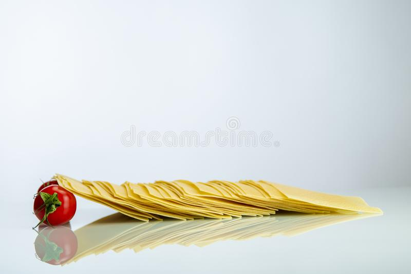 Tomaten, die Lasagnereihe auf weißem Reflexivglas stützen stockbilder