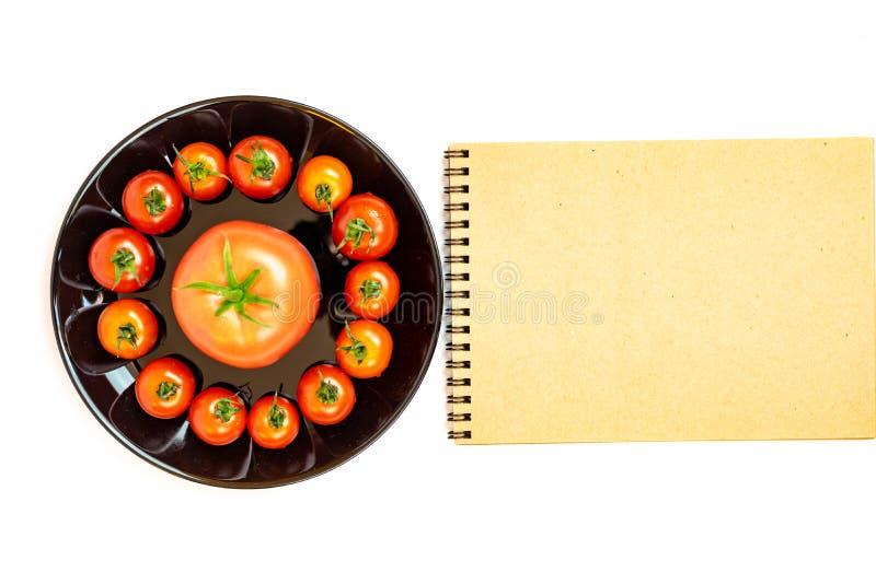 Tomaten in einem Schwarzblech lokalisiert auf wei?em Hintergrund nahe einem Notizblock Zusammensetzung von roten Tomaten in einer stockfoto