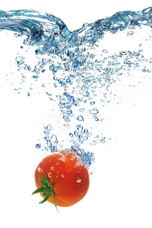 Tomaten faller djupt under vatten royaltyfria foton