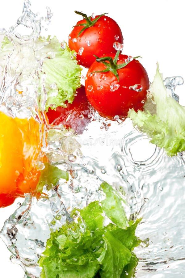 Tomaten, gelber Pfeffer und Kopfsalat im Spritzen stockfotos