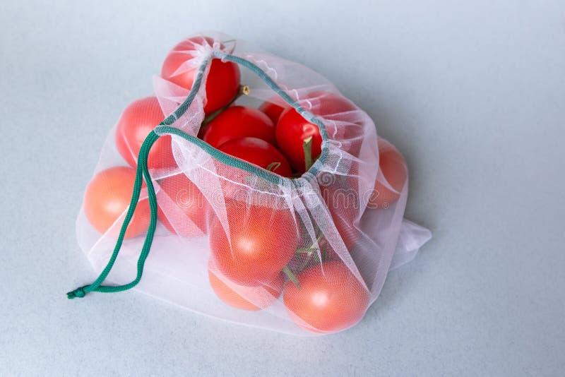 Tomaten im umweltfreundlichen Verpacken Wiederverwendbare Taschen für Gemüse und Früchte Einkaufen im Speicher, im Kleinen Umwelt lizenzfreie stockfotos