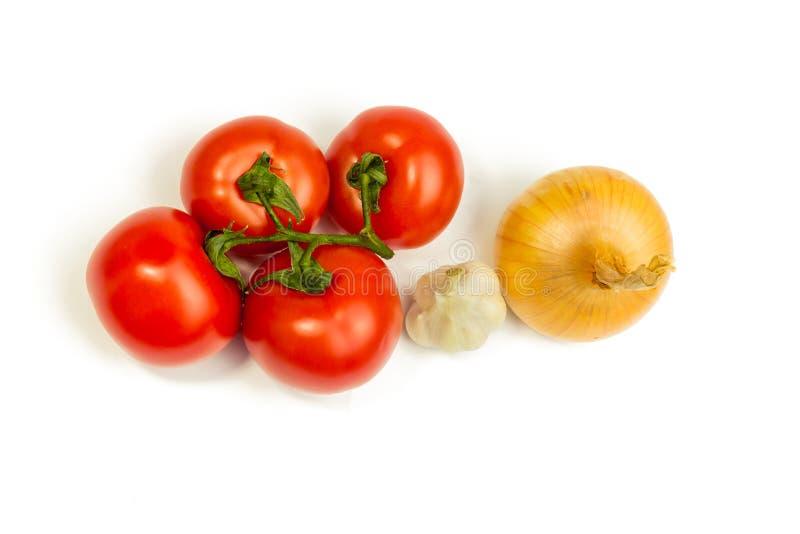 Tomaten, Knoblauch, Zwiebel auf einem weißen Hintergrund Er wird lokalisiert stockbild