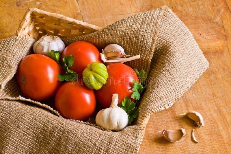 Tomaten, knoflook en peterselie in mand stock foto