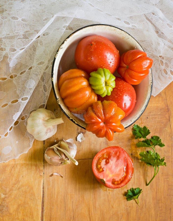 Tomaten, knoflook en peterselie op een lijst royalty-vrije stock foto