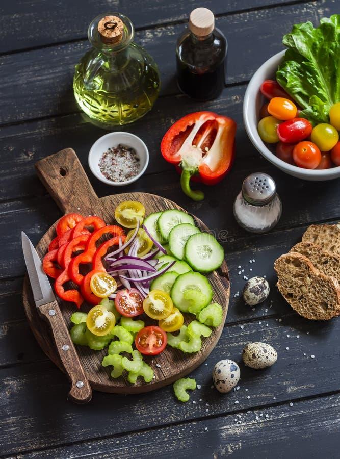Tomaten, komkommer, selderie, groene paprika, rode ui, kwartelseieren, olijfolie, balsemieke azijn, tuinkruiden en kruiden - Ingr stock afbeelding