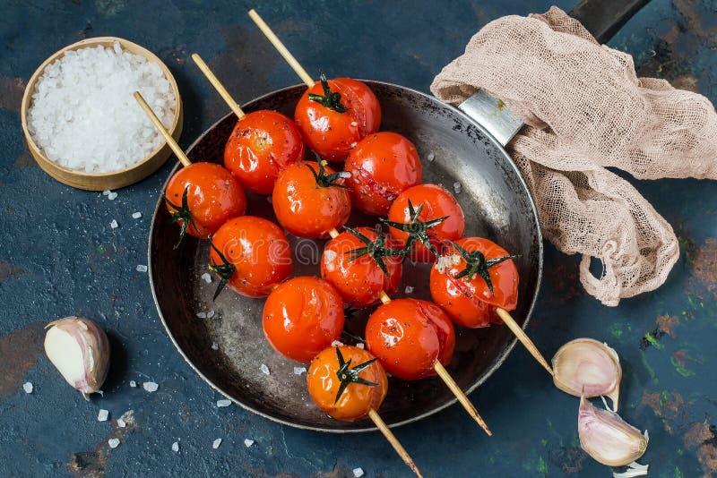Tomaten op vleespennen met olijfolie, knoflook, zout worden geroosterd dat stock afbeeldingen