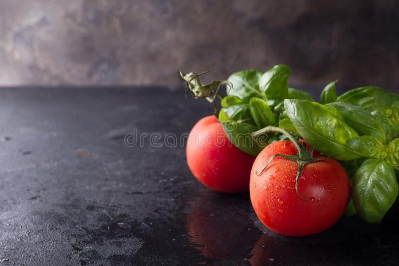 Tomaten und Basilikumblätter stockfotografie