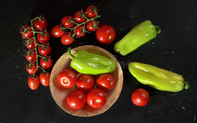 Tomaten und grüner grüner Pfeffer in der kleinen Schüssel und auf schwarzem Brett, Ansicht von oben stockbild