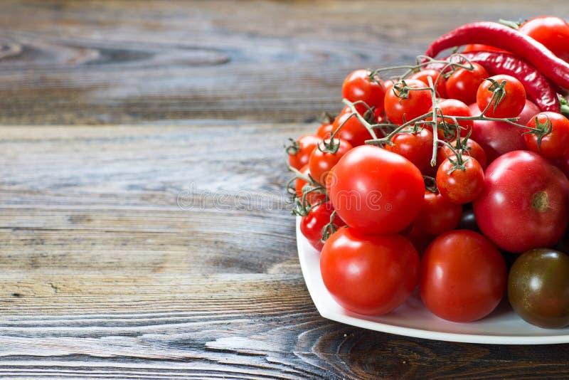 Tomaten van verschillende soorten op een witte schotel stock fotografie