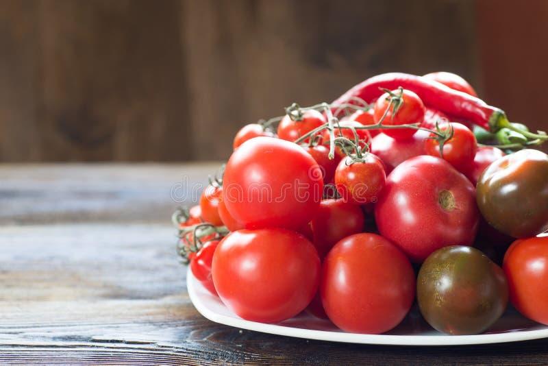 Tomaten van verschillende soorten op een witte schotel stock foto's