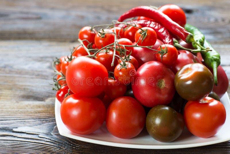 Tomaten von verschiedenen Arten auf einem weißen Teller lizenzfreies stockbild