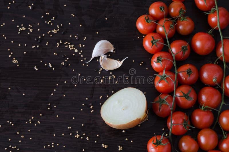 Tomatenkers met de helft van ui en knoflook aan kant stock fotografie