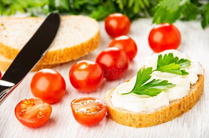Tomatenkirsche, Messer, Stücke Brot, Sandwich mit geschmolzenem Käse, Petersilie auf Tabelle stockfotografie
