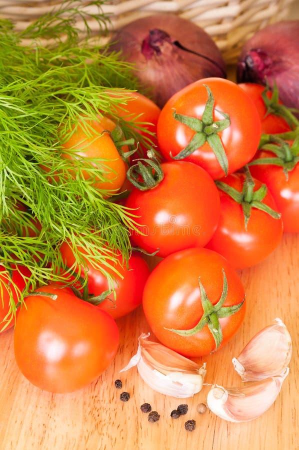 Tomatenknoblauchzwiebeln und -kräuter auf dem Tisch stockfotos
