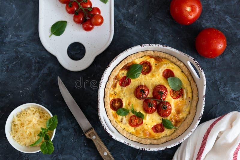 Tomatenpastei met basilicumbladeren, kippenans kaas met ingrediënten op donkere achtergrond Eigengemaakte Franse quiche Hoogste m stock foto's