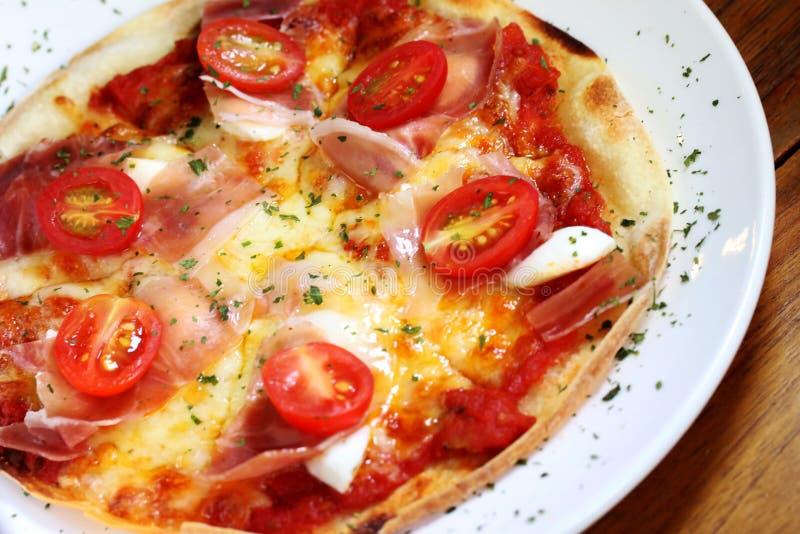 Tomatenpizza op de lijst stock afbeeldingen