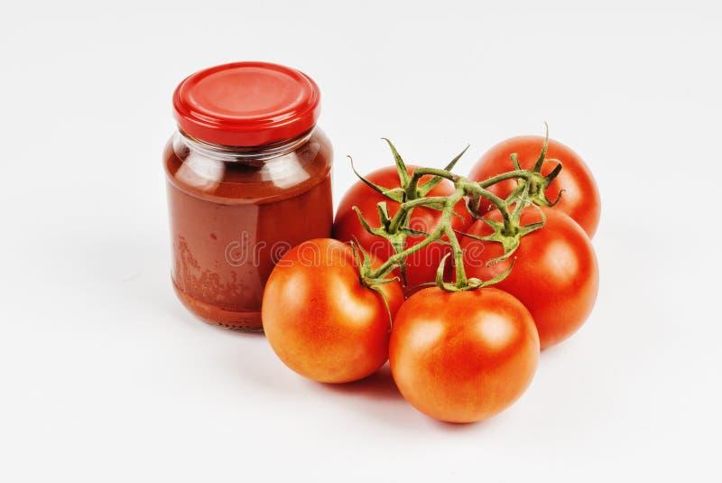 Tomatenpuree in een kruik en tomaten royalty-vrije stock afbeelding