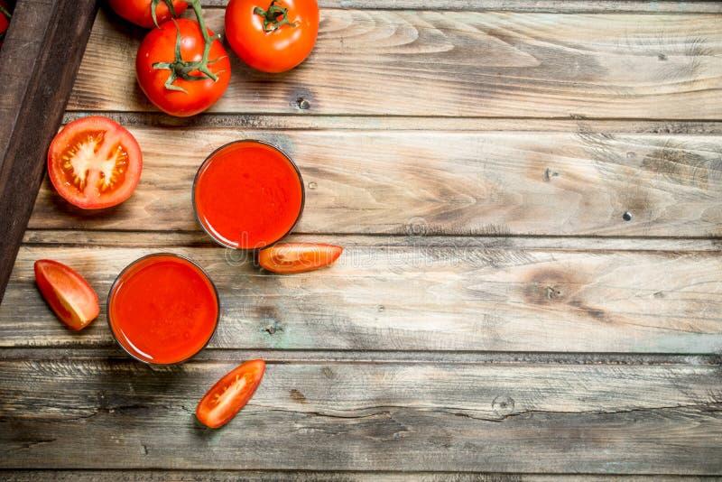 Tomatensaft in den Scheiben eines Glases und der Tomate stockbild