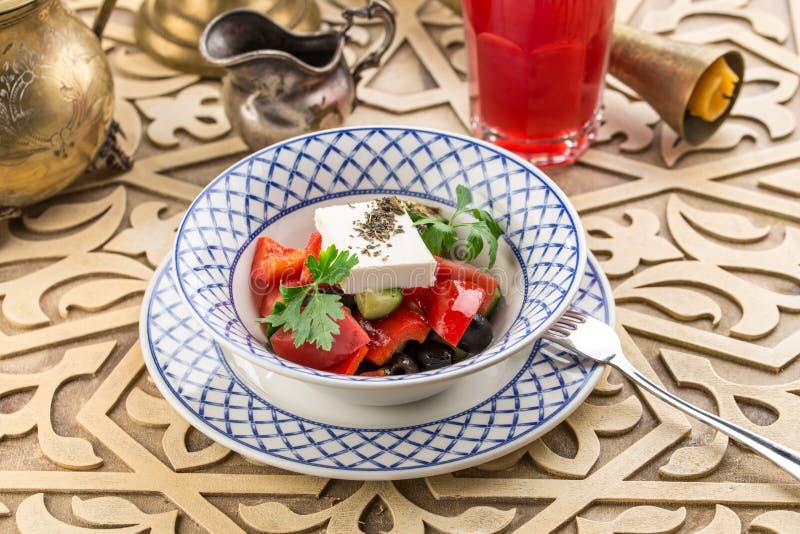 Tomatensalade met feta-kaas en kruiden op oosterse lijst royalty-vrije stock afbeeldingen