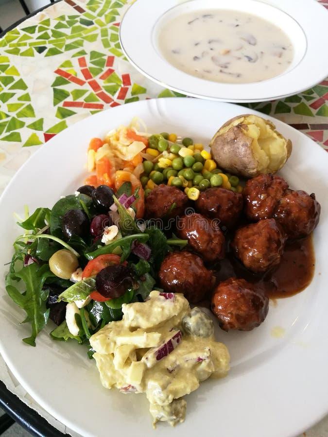 Tomatensauce der Fleischklöschen würziges süßes und saures mit Frischgemüse, Kartoffelsalat und Weiche kochte Kohlkarotte, Mais u lizenzfreie stockbilder