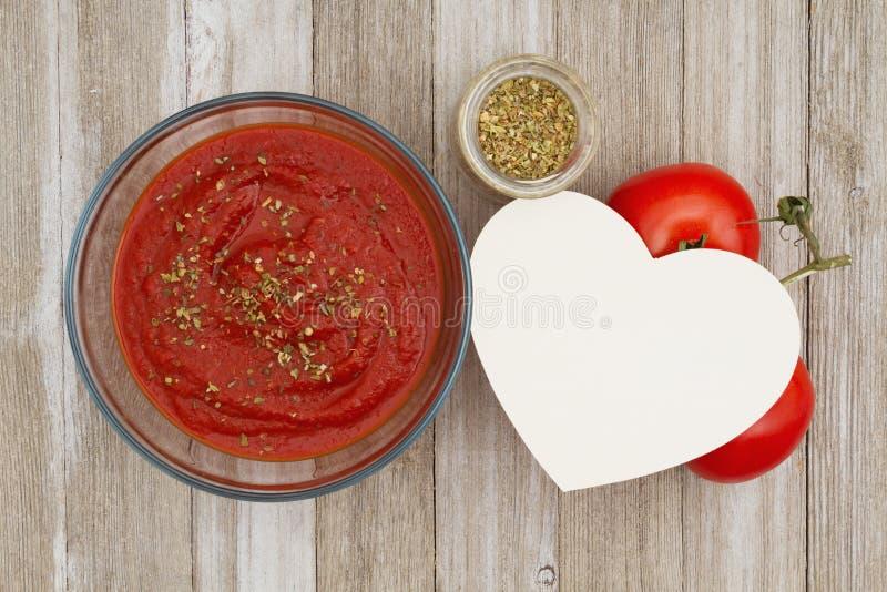 Tomatensaus in duidelijke kom met oregokruid en rode wijnstok rijpe tomaten op doorstane houten achtergrond royalty-vrije stock foto's