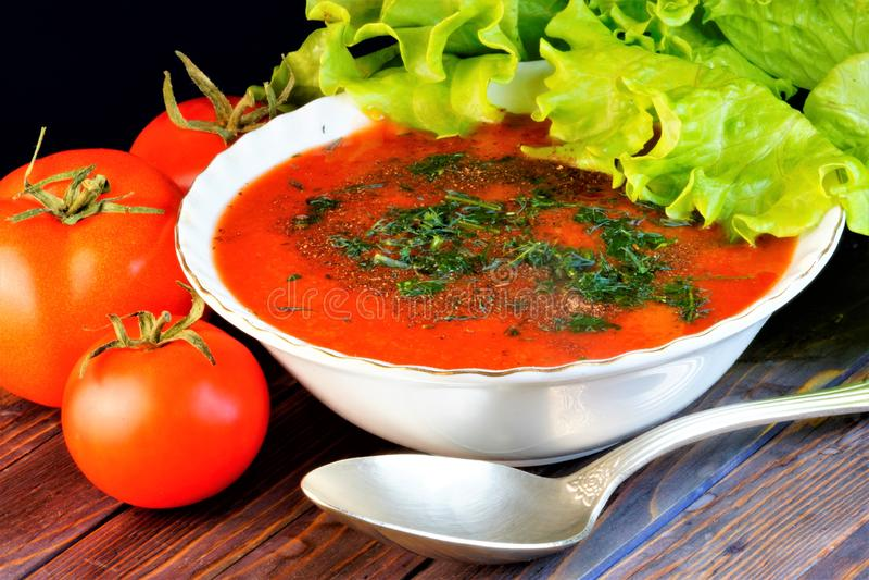 Tomatensoep en vegetarische saladegreens De rode tomaat is een populaire grote bes Kruidachtige installatie Smakelijk en gezond v stock fotografie