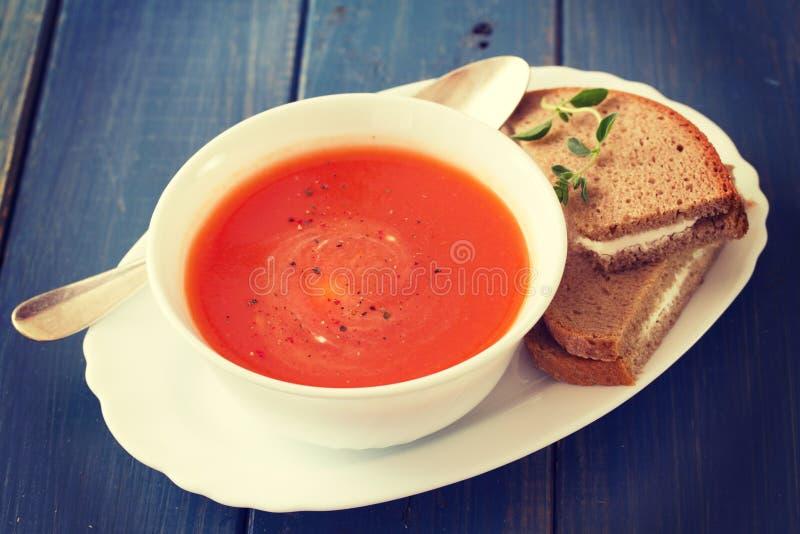 Tomatensoep in witte kom met sandwich op blauwe achtergrond stock afbeelding