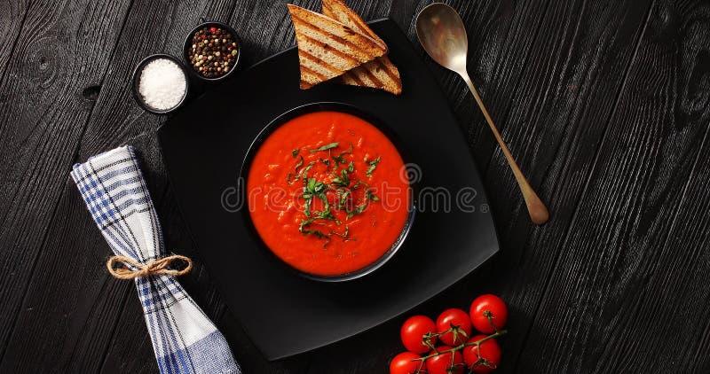 Tomatensuppe in der schwarzen Schüssel mit klarem Brot lizenzfreies stockfoto