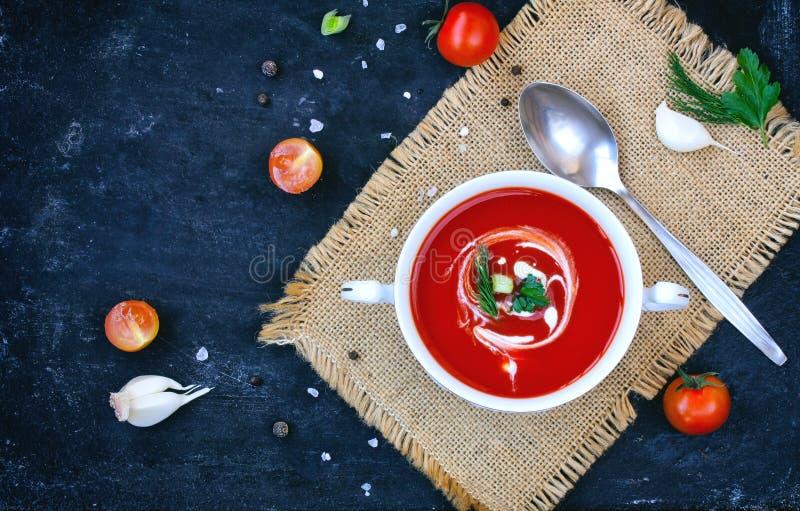 Tomatensuppe in einer weißen Schüssel auf schwarzer Tabelle stockfoto