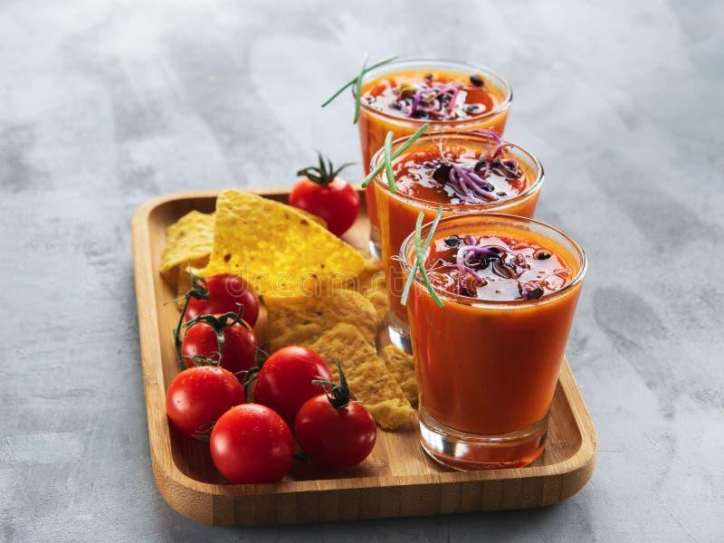 Tomatensuppe gazpacho in den Gläsern mit den gekeimten Sprösslingen begleitet mit Corn chipen auf hellgrauem Hintergrund vertikal stockfotografie