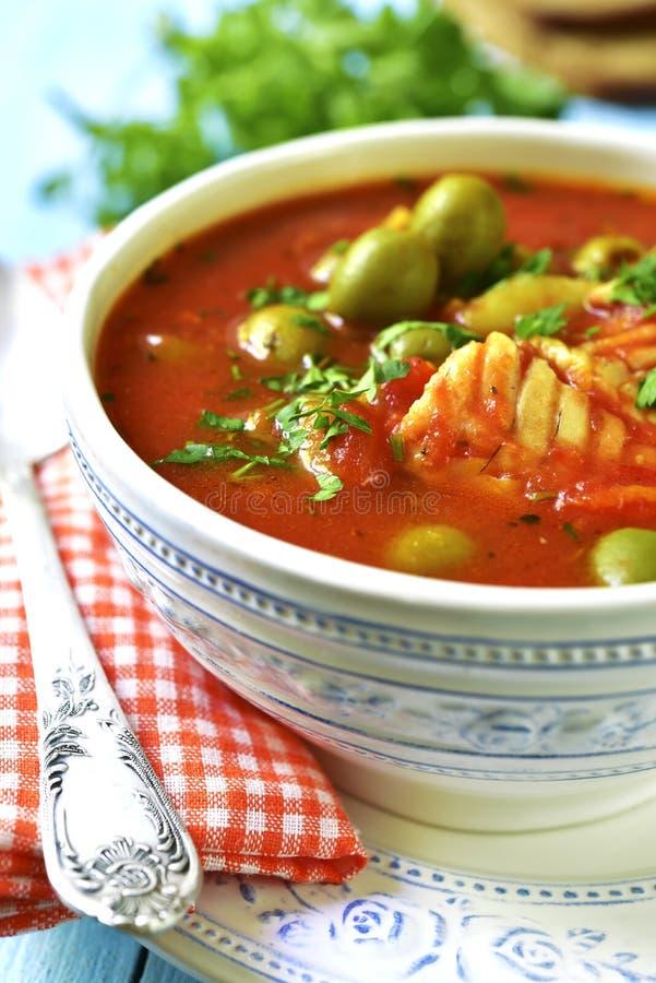 Tomatensuppe mit Kabeljau, Kartoffel und Oliven lizenzfreie stockbilder