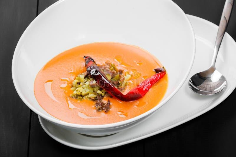 Tomatensuppe, Suppe des roten Pfeffers, Soße mit Olivenöl, Fleisch und Essiggurken in der Schüssel auf schwarzem hölzernem Hinter lizenzfreie stockfotos