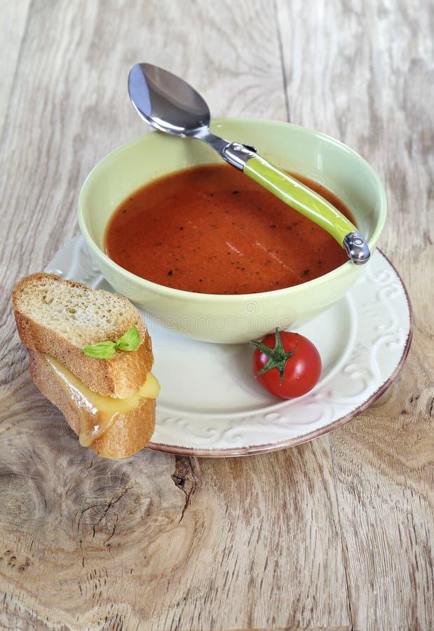Tomatensuppe und Scheiben des Stangenbrots mit Käse lizenzfreies stockbild