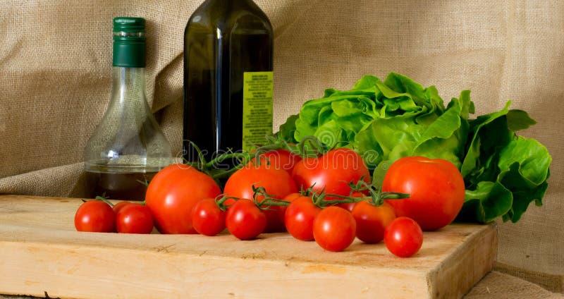Tomater, grön sallad, olivoljaflaska och genomskinlig flaska för vinäger arkivfoto