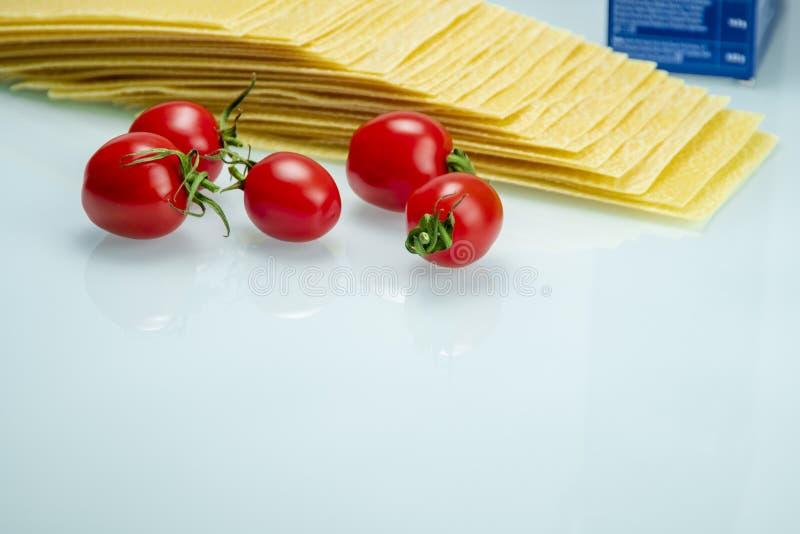 Tomater med lasagner på vitt reflexivt exponeringsglas arkivfoto