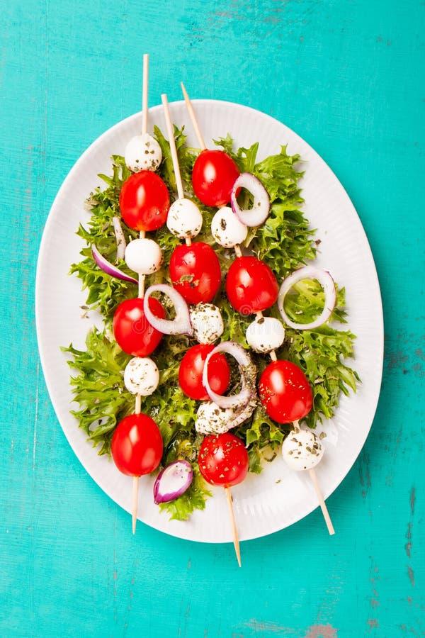 Tomater och mozzarella på pinnar på salladsidor arkivfoton