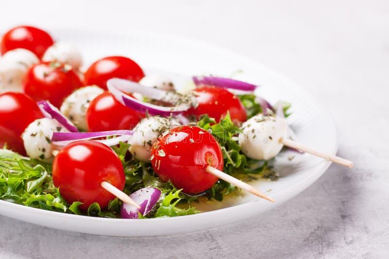 Tomater och mozzarella på pinnar på salladsidor royaltyfria bilder