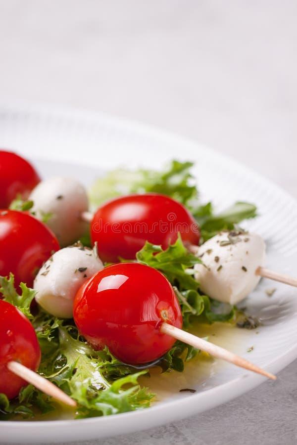 Tomater och mozzarella på pinnar på salladtjänstledigheter arkivfoton