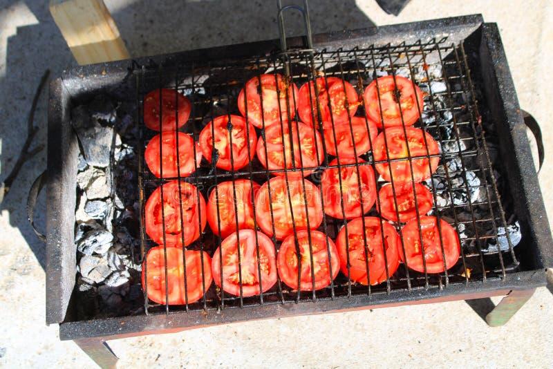 Tomater ordnar till för att laga mat på gallret royaltyfria bilder