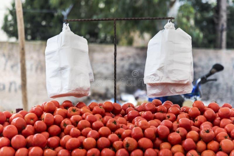 Tomater på ett utomhus- stånd, utomhus- sunda frukter för folk med vita plastpåsar för att shoppa arkivfoton