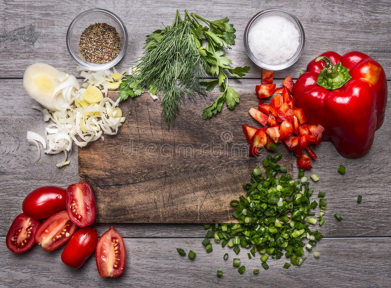Tomater, purjolökpersilja och dill högg av salladslöken för röd peppar på en bästa sikt för träskärbrädaträbakgrund royaltyfri fotografi
