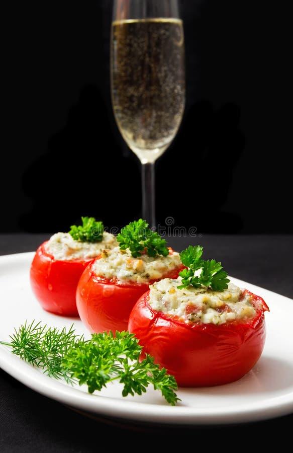 Tomater som är välfyllda med ost och dekorerar med nya örter royaltyfria bilder