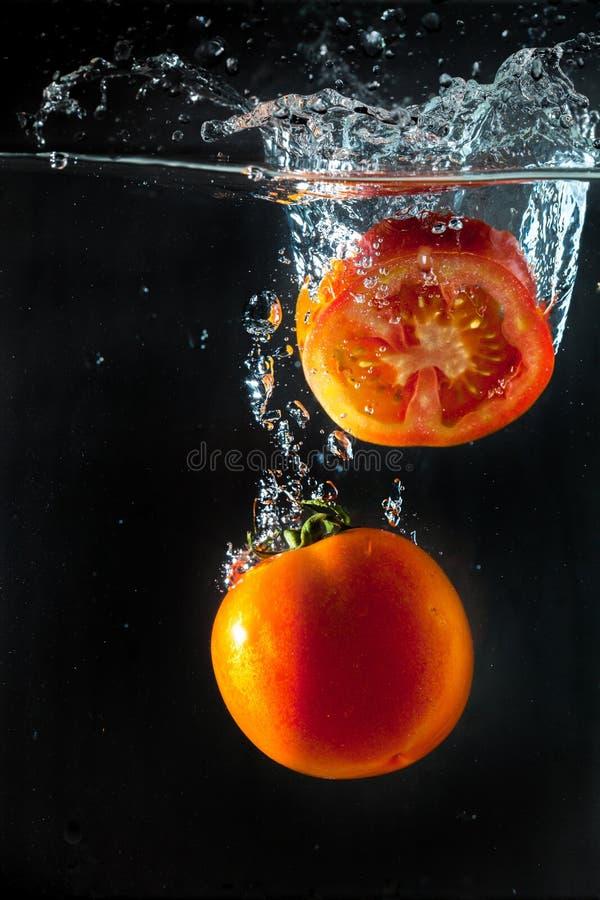 Tomater som plaskar med i vatten arkivbild