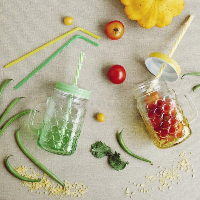 Tomates, épices, fruits, légumes, un bol en verre avec une paille sur la table image libre de droits