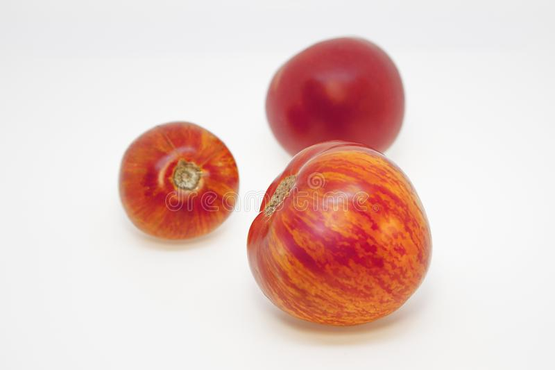 Tomates abigarrados y tomate rojo con el modelo natural inusual Tres tomates inusuales hermosos imagen de archivo