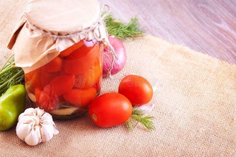 Tomates adobados en tarros con las especias y las verduras en una tabla fotos de archivo